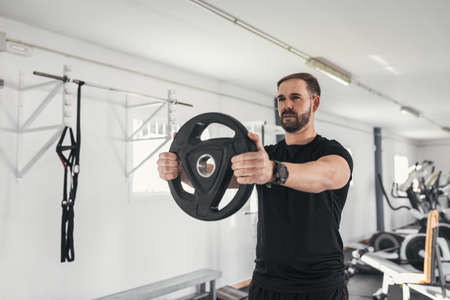 man caucasian handsome and big muscle in sportswear. Young man holding weights during an exercise class in a gym. Healthy sports lifestyle, Fitness concept.