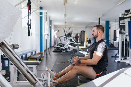 Young man Doing Heavy Weight Exercise For Back On Machine, Focus on him. Concept of health.