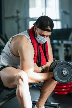 Man with mask doing biceps exercises with dumbbells in the gym. sitting on a bench. Covid19, coronavirus. Health and wellness concept