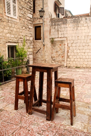 Outdoor cafe with wooden furniture in old town. Summer rain photo