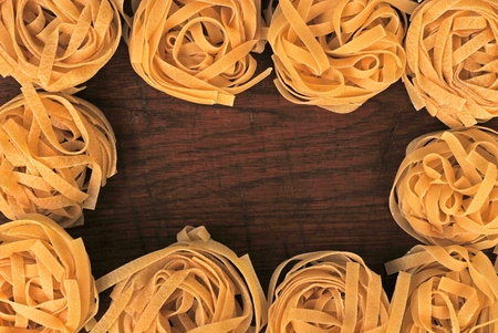 Yellow tagliatelle italian pasta border on wooden background Stock Photo - 10369558