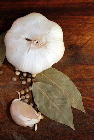 garlics: Garlic bulb and clove with spices on wooden cutting board (vertical image)