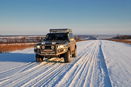 snow road with car 4x4 in sunny winter day photo