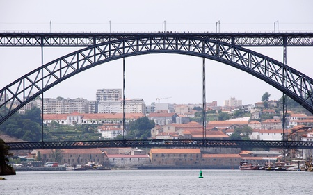 Horizontal sityscape with famous steel bridge and river Douro in Porto(Portugal) photo