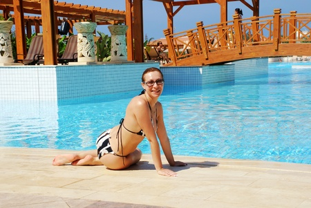 pergola: Smiling woman sitting near swimming pool in luxury hotel