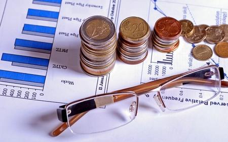 ガラスおよび硬貨は金融のグラフィックと紙のシートに横たわっています。