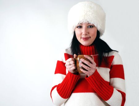 winter portrait of young beautiful girl in fluffy hat with hot cup  photo