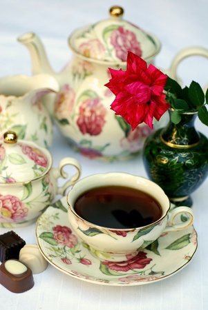 Traditional english tea with floral dishware and rose.Selective focus photo