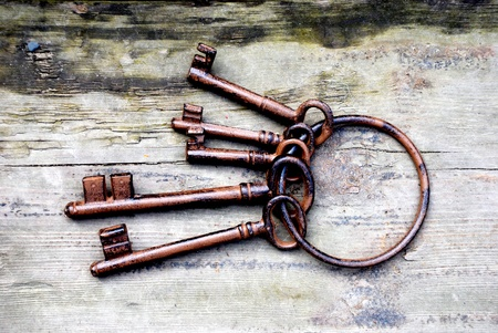 Antique copper keys on old wooden background Stock Photo