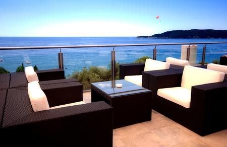 Терраса гостиная с креслами из ротанга и видом на море в элитном курорте. Редакционное