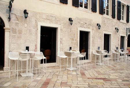 Прекрасный вид с белыми столиками и стульями на тротуаре кафе в старом городе Средиземноморья (Италия)