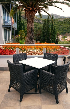 Al fresco seats on the mediterranean hotel terrace with flowers and mountains view