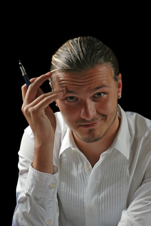 Portrait of handsome pensive young smiling office manager with pen on black background Stock Photo - 11673844