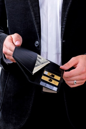 man holding a wallet with dollars and credit cards photo
