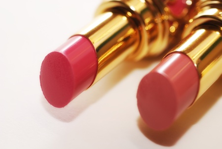 Pair of open tube of pink luxury lipstick. Selective focus photo