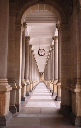 Перспективный вид классической набережной с колоннами и часы (Карловы Вары, Чехия) Фото со стока