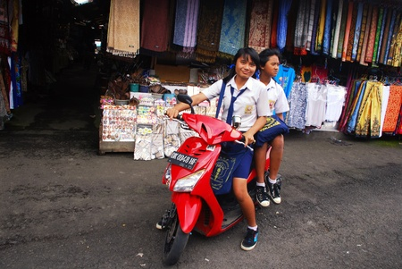 BALI, INDONESIA - JANUARY 4: Two indonesian schoolgirls with a scooter on January 4, 2011 on traditional asian street market in Bali, Indonesia. The use of scooters and motorbikes as transport for people of all ages is very popular in Bali.