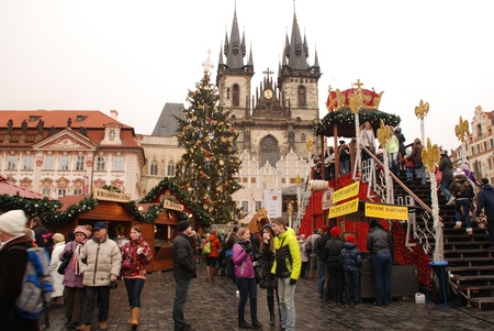 Prague,Czech Republic-December 29,2011: Tourists and local people on the Christmas market, on the Old Town Square. The Prague Christmas markets consist of brightly decorated wooden huts selling traditional Czech products from handicrafts and hot food. The