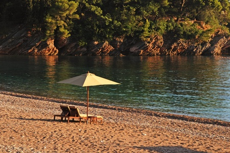 Two deck chairs and umbrella on the beach in rocky bay in a beautiful summer afternoon. Mediterranean sea photo