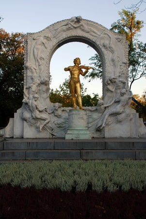 The golden statue of music composer Johann Strauss in StadtPark in Vienna, Austria. Fall afternoon light photo