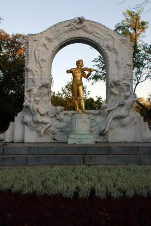 musique: The golden statue of music composer Johann Strauss in StadtPark in Vienna, Austria. Fall afternoon light