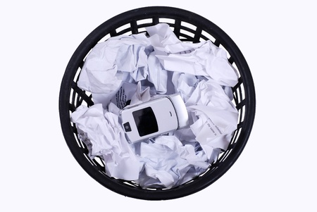 isolated full wastepaper with crumpled papers and mobile phone  photo
