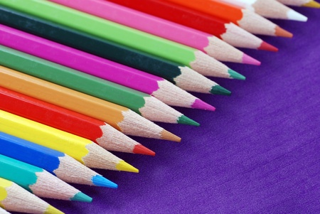 Multicolored crayons in a row on purple background Stock Photo - 12231271