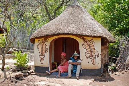 CULTURAL VILLAGE LESEDI, SOUTH AFRICA- JANUARY 1: African sotho couple wearing traditional handmade dress sitting near native tribal house on January 1, 2008. Sotho people are distinguished by their thick colourful blankets and conical hats.Sotho сlans w