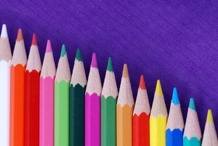 Multicolored crayons in a row on purple background Stock Photo - 12231578