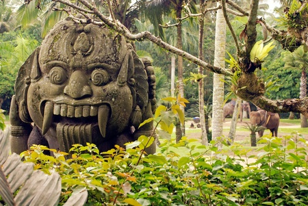 Statue of Balinese demon in jungle. photo