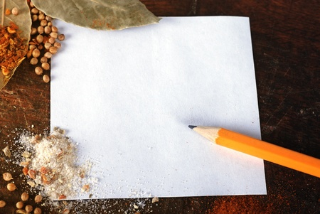 note to write recipes on the background of a wood cutting board with spices photo