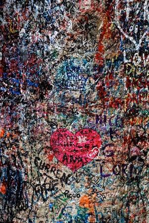 Вертикальные изображения с любовью сообщений и сердца на знаменитой стене Ромео и Джульетта дом (Верона, Италия)
