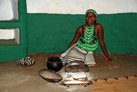 LESEDI CULTURAL VILLAGE, SOUTH AFRICA - JAN 1: Zulu woman wearing handmade clothing  cooking maize meal in tribal house of  on January 1, 2008 at the Lesedi Cultural Village, South Africa.Three basic Zulu ingredients-maize meal, sorghum and beans-are trad