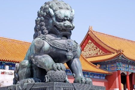 Ancient bronze lion and red chinese pavilliones in Emperor Forbidden city(Beijing, China)