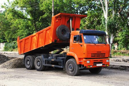 Orange industrial truck on construction of road