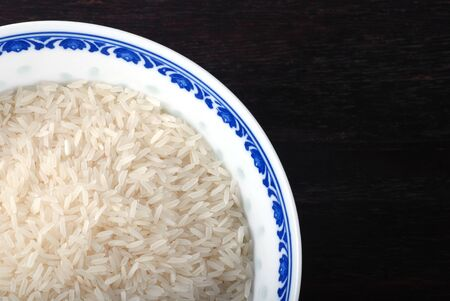Chinese blue bowl of uncooked white rice on dark wooden background. photo