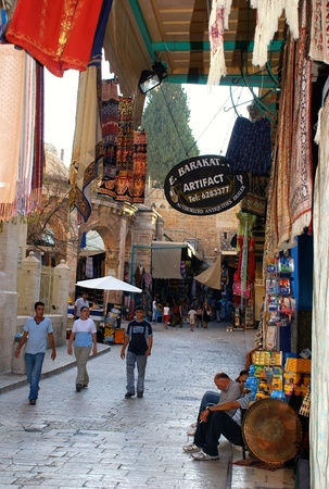 Jerusalem, Israel - July 23, 2007: East market on narrow streets in Jerusalem Old City.The Old City is divided into four vaguely defined quarters: Christian, Armenian, Jewish and Muslim. This quarters has many small shops where you can buy fabrics, artifa