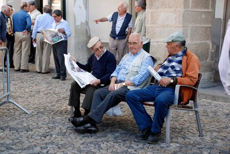 EVORA, PORTUGAL - MAY 03: Group of old portugal men on a bench are reading newspapers and discussing news of today on May 03,2009 in center of Evora,Portugal. Évora is ranked number two in the Portuguese most livable cities survey of living conditions. I