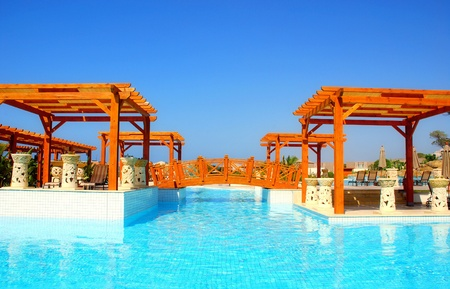 Panoramic summer landscape with swimming pool , wooden foot-bridge and pergola in resort hotel(Turkey)