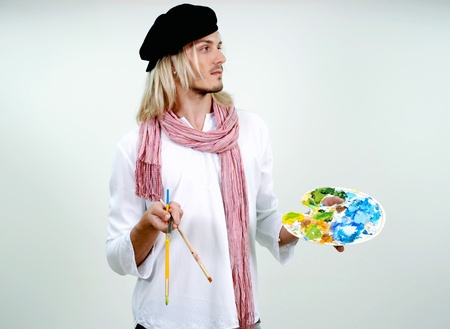 portrait of young beautiful artist with palette and paintbrushes photo