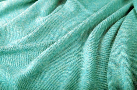 Light green crumpled luxury cashmere background. Selective focus photo