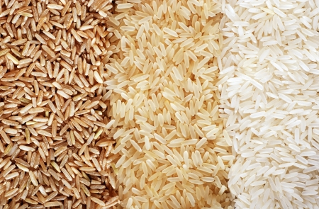 bran: Food background with three rows of rice varieties : brown rice, mixed wild rice, white (jasmine) rice.  Stock Photo