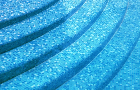 curved steps at the resort swimming pool with mixed blue tile mosaic