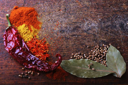 Spices on a old wooden cutting board with saffron, curry and chili pepper photo