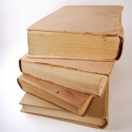 Pila di vecchi libri su sfondo grigio chiaro.