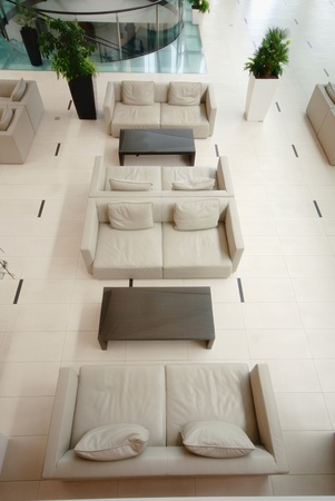 Contemporary lobby area from above with modern furniture, beige sofas and tile floor in luxury hotel .