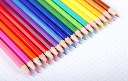 Multicolored crayons in a row on white squared paper background. Stock Photo - 13802760