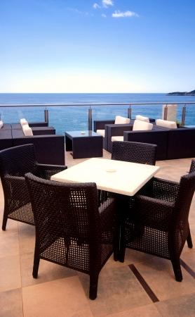 malacca: Poltrone in rattan nel salotto con terrazza con vista mare in un resort di lusso.