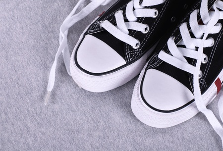 A pair of black canvas sneakers on grey textile background with copyspace photo