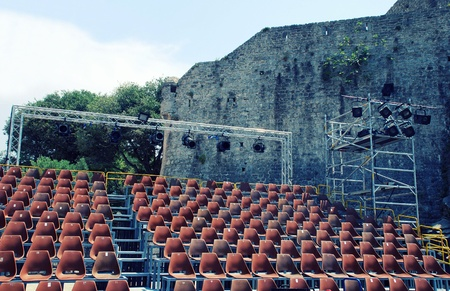 Empty vintage seats and spotlights in an open-air theater with medieval wall on background(Budva, Montenegro) photo